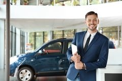 Salesman with tablet in modern car. Dealership royalty free stock photography