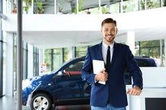 Salesman with tablet. In modern car dealership stock image