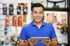 Salesman with tablet pc in the shop. Portrait of Asian salesman standing with digital tablet and smiling at camera in workshop stock photo