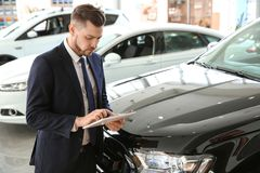 Salesman with tablet in salon. Buying new car royalty free stock images