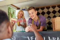 Salesman taking customer credit card at food truck stock photos