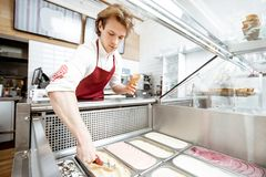 Salesman making ice cream in the pastry shop. Salesman taking ice cream from the trays on the showcase refrigerator and putting into the waffle cone in the stock photo