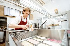 Salesman making ice cream in the pastry shop. Salesman taking ice cream from the trays on the showcase refrigerator and putting into the waffle cone in the stock photos