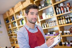 Salesman taking inventory in wine shop. Man stock photography