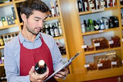Salesman taking inventory in wine shop. Wine Stock Images