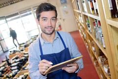 Salesman taking inventory in wine store. Sommelier royalty free stock image