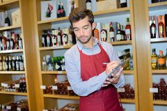 Salesman taking inventory in wine store. Sommelier stock images