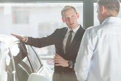 Salesman talking about car. Photo of elegant salesman talking about new car model royalty free stock photos