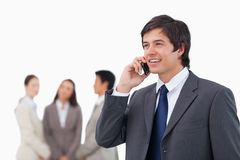 Salesman talking on cellphone with colleagues behind him Royalty Free Stock Photo