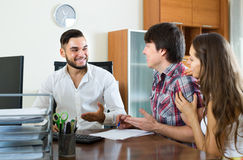 Salesman talking about contract with couple. Happy couple and salesman talking about business contract in the office stock images