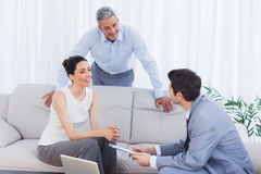 Salesman talking with customers on couch. At home stock images