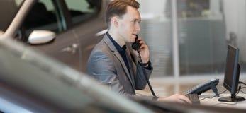 Salesman talking on landline phone in showroom. Side view of salesman talking on landline phone in car showroom royalty free stock photo