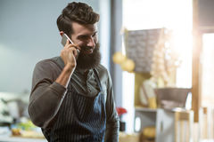 Salesman talking on mobile phone at counter royalty free stock photos