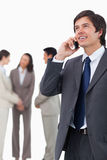 Salesman talking on mobile phone with team behind him royalty free stock image