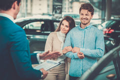 Salesman talking to a young couple at the dealership  showroom. Stock Image
