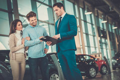Salesman talking to a young couple at the dealership showroom. royalty free stock photography