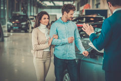 Salesman talking to a young couple at the dealership  showroom. Stock Photo