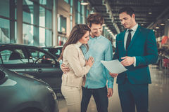 Salesman talking to a young couple at the dealership showroom. royalty free stock images