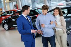 Salesman talking to a young couple at the dealership  showroom. Stock Photography