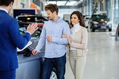 Salesman talking to a young couple at the dealership  showroom. Royalty Free Stock Photos
