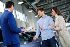 Salesman talking to a young couple at the dealership showroom. royalty free stock photo