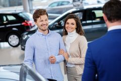Salesman talking to a young couple at the dealership showroom. stock images