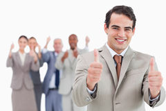 Salesman with team behind him giving thumbs up Stock Photo