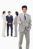Salesman with team behind him offering hand Stock Photo