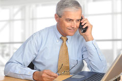 Salesman on Telephone. A mature salesman talking on the telephone. The man is seated in a modern office with a laptop on his desk in front of a large bank of stock photos