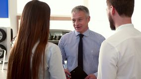Salesman tells the couple about the car at the dealership. Mature salesman telling the couple about the car at the dealership. Close up of young people royalty free stock images