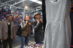 Salesman of ties on the design market Spitalfield shows how to t. LONDON - August 27, 2016: salesman of ties on the design market Spitalfield shows how to tie a stock photography