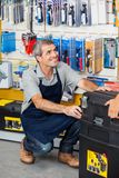 Salesman With Tool Box In Store. Full length of mature salesman with tool box in hardware store royalty free stock image