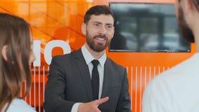 Salesman transmitting keys to young couple in car dealership.