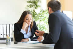 Salesman trying to convince to a bored client. Bad salesman trying to convince to a bored client in her office or businessman in a job interview Royalty Free Stock Image