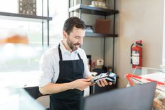 Salesman Using Credit Card Reader In Store. Confident baker inserting credit card in POS terminal at shop royalty free stock photos