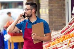 Salesman using his mobile phone in health grocery shop. Shot of salesman using his mobile phone in health grocery shop stock photography