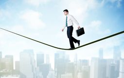 Salesman walking on rope above the city Stock Photography