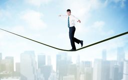 Salesman walking on rope above the city Royalty Free Stock Photography