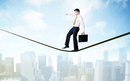 Salesman walking on rope above the city Royalty Free Stock Photos