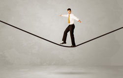 Salesman walking on rope in grey space Royalty Free Stock Photography