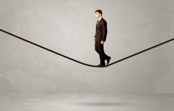 Salesman walking on rope in grey space Stock Image
