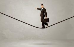 Salesman walking on rope in grey space Royalty Free Stock Images