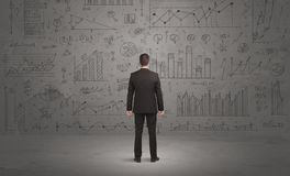 Salesman With Business Charts On Wall Royalty Free Stock Photos