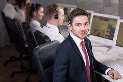 Salesman at work. Young smiling salesman working in call center stock images