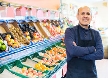 Salesman working in fruit section. Charming elderly salesman working in fruit section of supermarket Stock Image