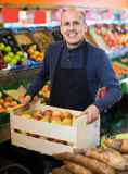 Salesman working in fruit section. Smiling mature salesman working in fruit section of supermarket Stock Images