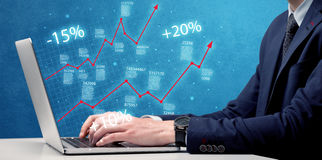 Salesman working on graph with laptop Stock Photography