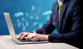 Salesman working on graph with laptop Royalty Free Stock Photography