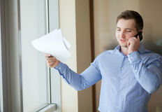 Salesman working from home and talking on phone.  stock image