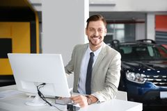 Salesman working in modern car dealership. Buying new auto stock photography